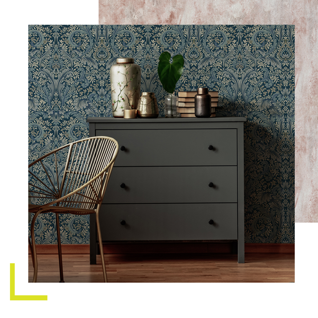 dark grey chest of drawers in front of teal patterned wallpaper