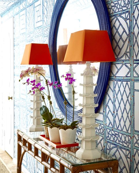 Wallpapered entryway with round blue mirror and two lamps