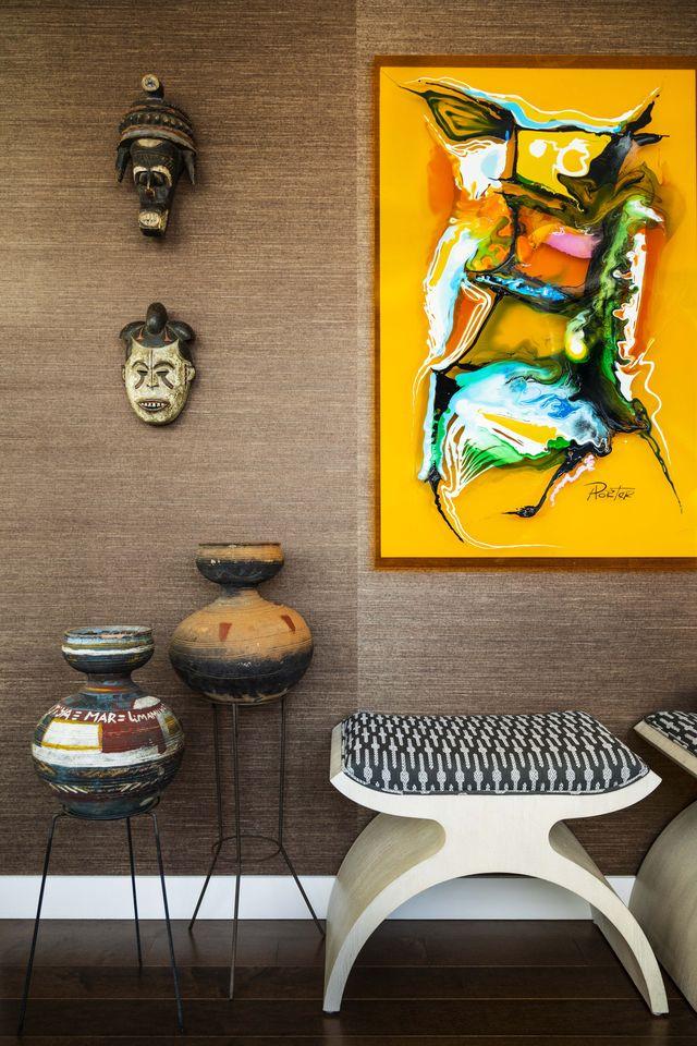 entryway, brown wallpaper, yellow artwork, vases
