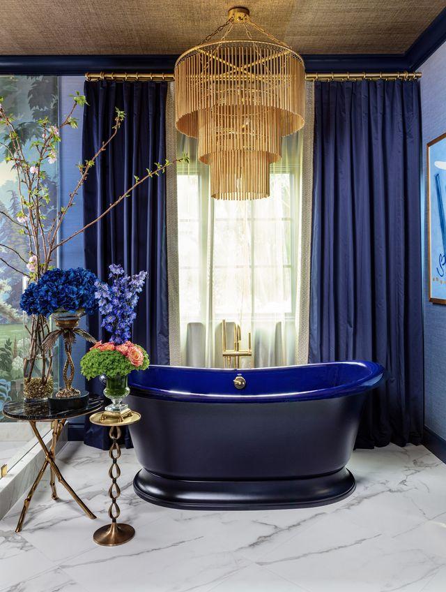 blue bathtub, blue curtains, gold chandelier, floral arraignment