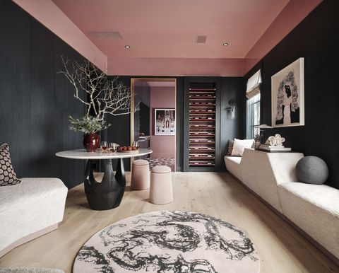 wine bar and tasting room, circular table, wall sofa, circular stool seats, pink ceiling, bark green painted walls