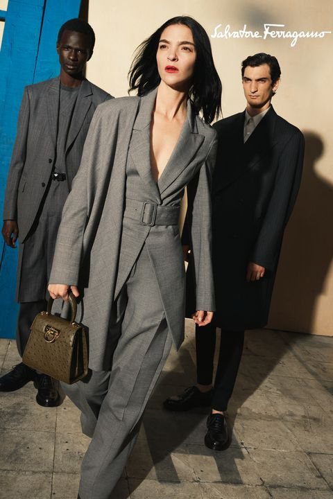 a model wearing a gray suit is flanked by two other models in the background, one wearing a charcoal suit and the other a black suit she wears bright red lipstick and holds a dark green handbag