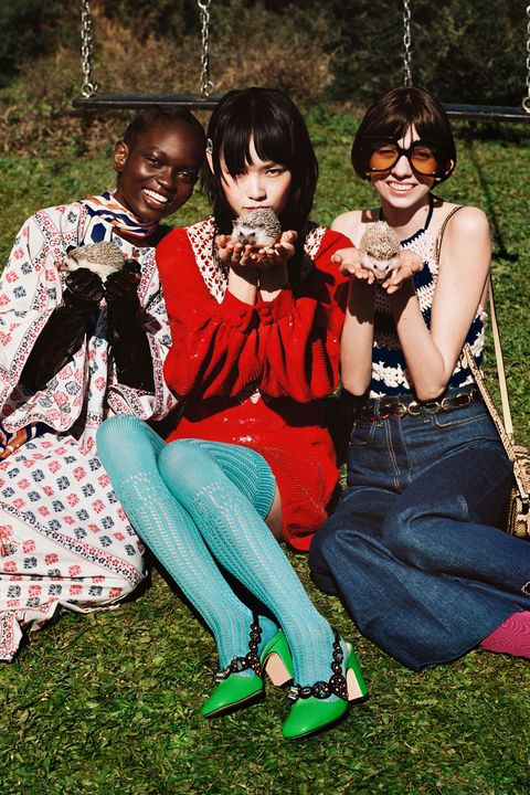 three models sit close together on grass, carrying hedgehogs in their hands