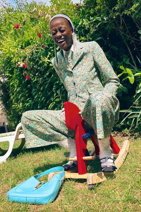 a model wearing a printed green and yellow floral suit, white fuzzy socks, and black ballet flats embellished with crystals sits on a tiny red wooden rocking horse in what appears to be a garden she's laughing
