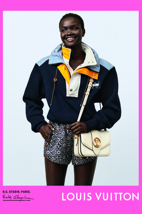 model stands against white backdrop, wearing printed lv shorts, a dark blue jumper, and carrying a white lv shoulder bag the photo has a hot pink border and says louis vuitton in the corner