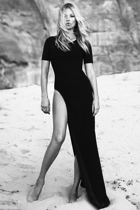 kate moss in black and white, wearing a black maxi dress with a high leg slit that shows her entire right leg the background seems to be of sand and rocks she holds a cigarette in her mouth