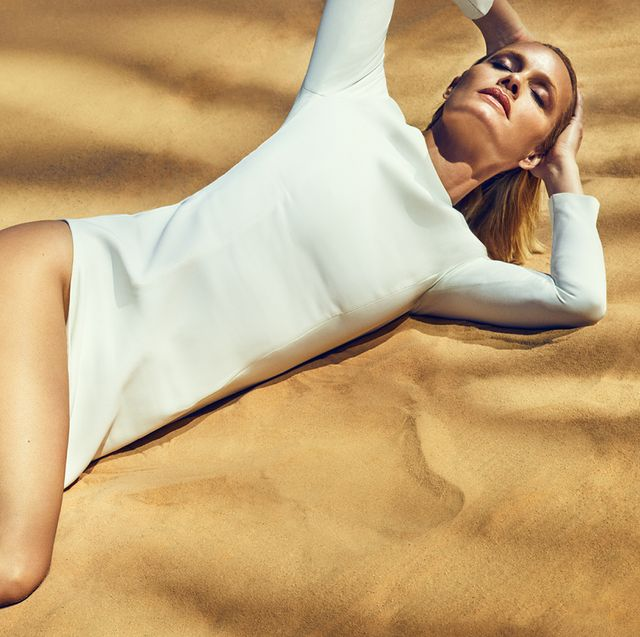 a blonde woman lays down on a background of sand, holding her hair back she wears a white long sleeved maxi dress with a revealing leg slit that starts above the right side of her waist