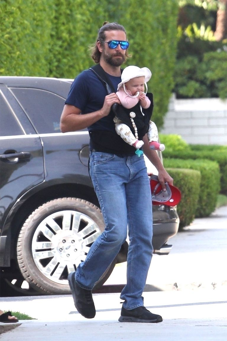 American actor Bradley Cooper carrying his new born daughter