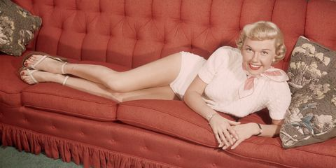 Blond, Leg, Beauty, Hairstyle, Thigh, Couch, Long hair, Sitting, Human body, Furniture,