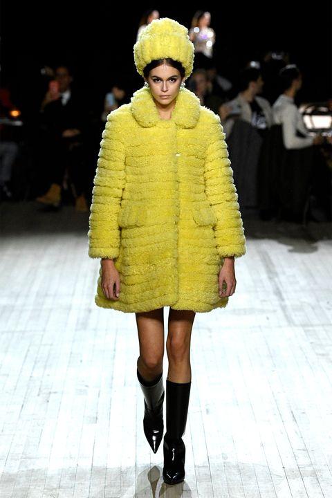 Fashion model, Fashion, Fashion show, Runway, Clothing, Fur, Yellow, Outerwear, Fur clothing, Footwear,