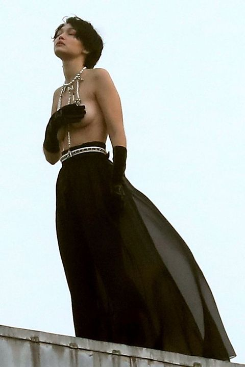 *PREMIUM-EXCLUSIVE* Gigi Hadid strikes a dramatic pose as she goes topless during a photoshoot for Chanel in Paris