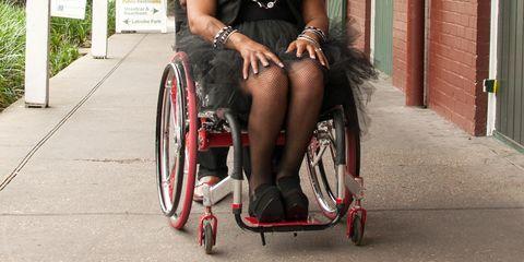 Wheelchair, Leg, Vehicle, Bicycle wheel, Mode of transport, Human leg, Thigh, Bicycle drivetrain part, Sitting, Disabled sports,