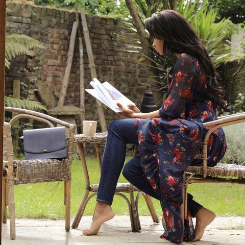 Textile, Human leg, Denim, Sitting, Bag, Street fashion, Chair, Knee, Thigh, Long hair,