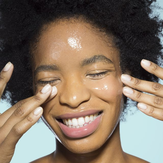 close up of young mixed race woman applying glossy face make up moisturizer, smiling, with eyes closed with turquoise background