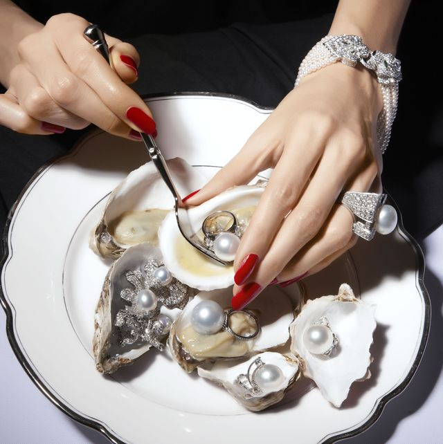 woman with red nail polish eating oysters with pearls inside