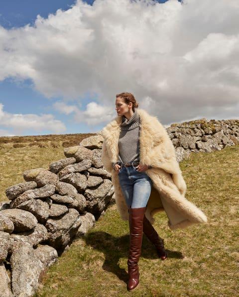 Fur, Photography, Rock, Grass, Outerwear, Cloud, Sitting, Coat, Stone wall, Photo shoot,
