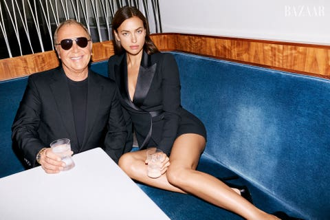 irina and michael sit in a blue booth wearing black blazers