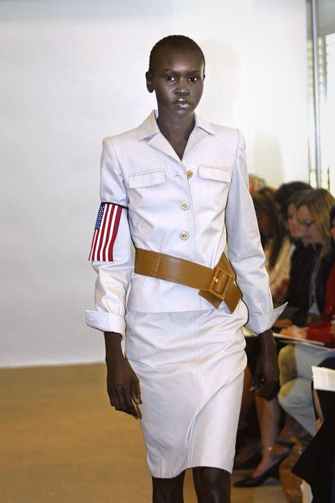 alek walks down runway in white jacket and skirt with american flag on sleeve