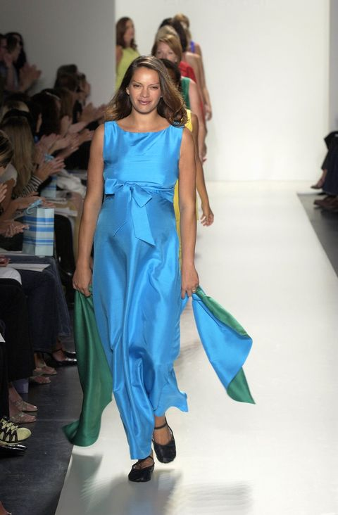 model walks down runway in blue and green dress