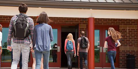 Teenagers walking into high school building