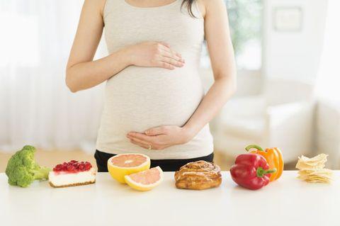 一個懷孕的女生前面擺著食物
