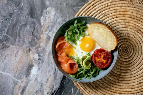 healthy breakfast bowl with fried eggs salmon avocado grilled tomato and salad serving with bread on straw napkin over dark marble background flat lay copy space