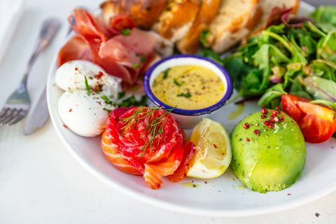 healthy breakfast with poached eggs, salmon, avocado and fresh salad
