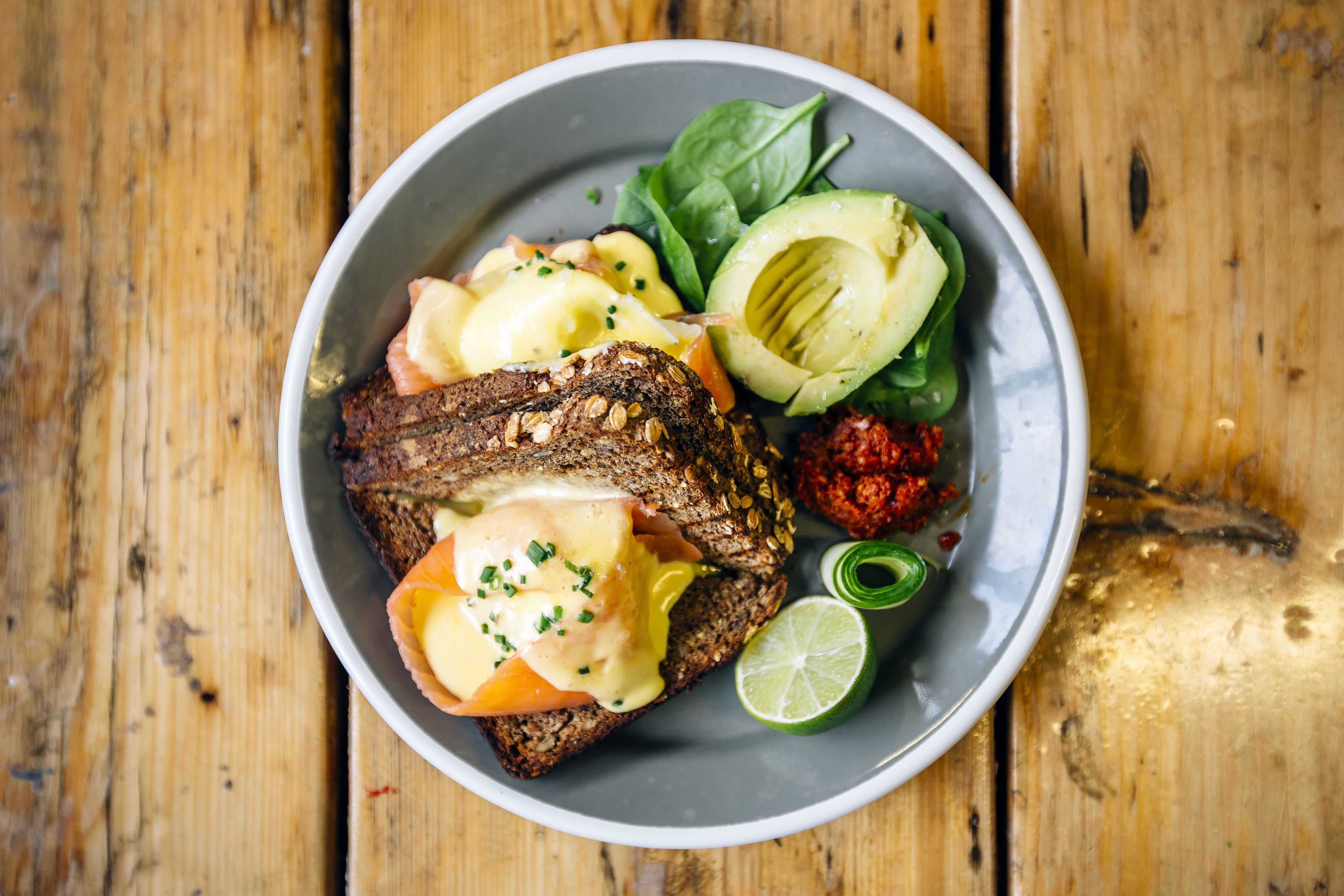 Healthy breakfast with rye bread, salmon, poached egg, avocado and lime