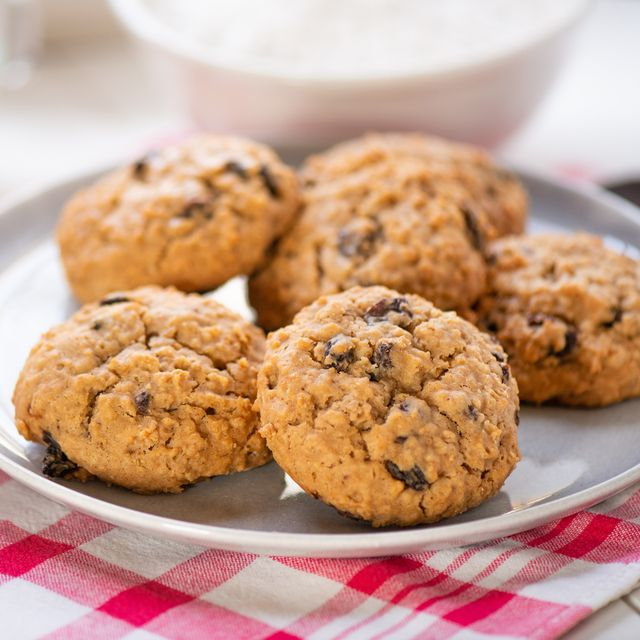 golden brown oatmeal cookie with raisins on a rustic red checked tablecloth