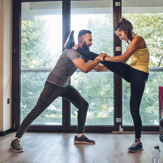 Healthy couple stretching at a gym