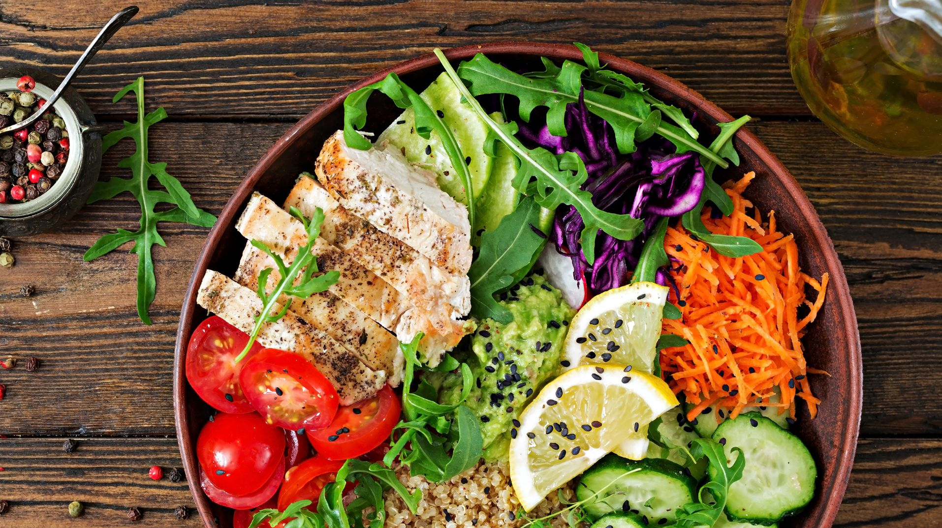 Healthy dinner. Buddha bowl lunch with grilled chicken and quinoa, tomato, guacamole, carrot, red cabbage, cucumber and arugula on wooden background. Flat lay. Top view. Banner