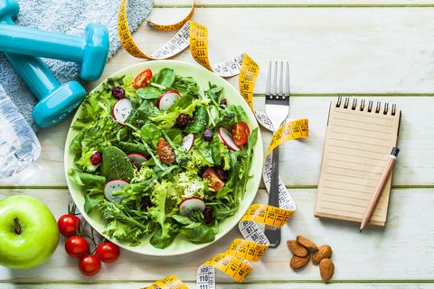 Healthy eating and exercising concepts: Fresh healthy salad, dumbbells and tape measure