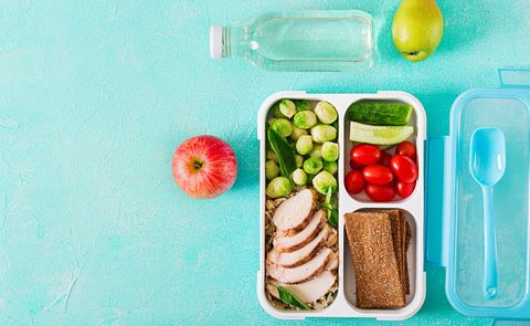 Healthy green meal prep containers with chicken fillet, rice, brussels sprouts and vegetables overhead shot with copy space. Dinner in lunch box. Top view. Flat lay
