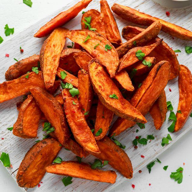 Healthy Homemade Baked Orange Sweet Potato wedges with fresh cream dip sauce, herbs, salt and pepper