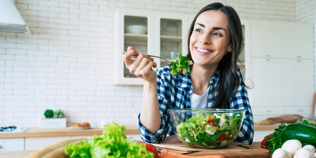 healthy lifestyle good life organic food vegetables close up portrait of happy cute beautiful young woman while she try tasty vegan salad in the kitchen at home