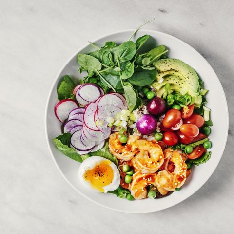 healthy lunch bowl with greens, avocado, cherry tomatoes, radish, boiled egg, and shrimp on white background