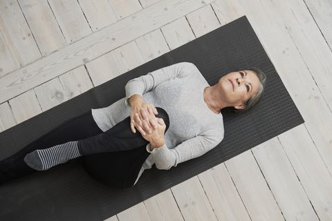 healthy mature woman stretching on yoga mat