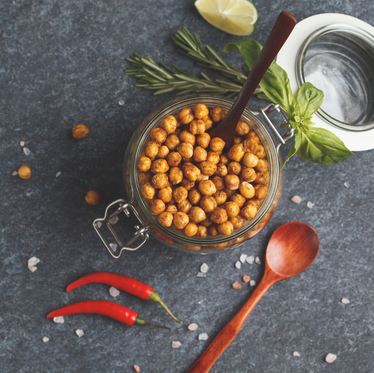 Healthy snack - baked spicy chickpeas in a glass jar, top view, copy space. Healthy vegan food concept.