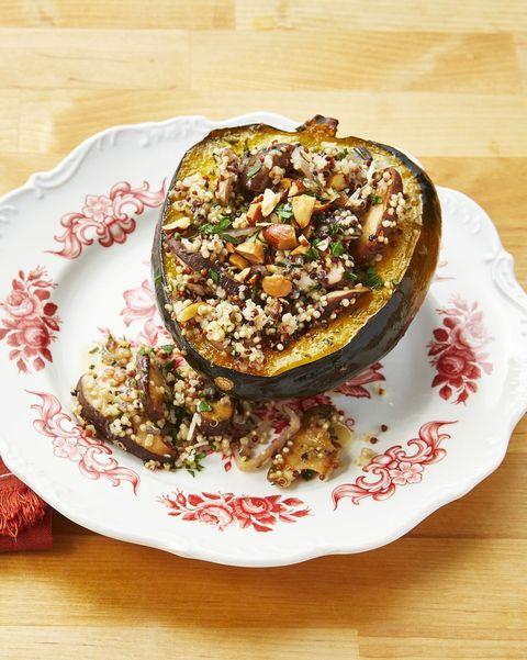quinoa and mushroom stuffed acorn squash on red and white plate