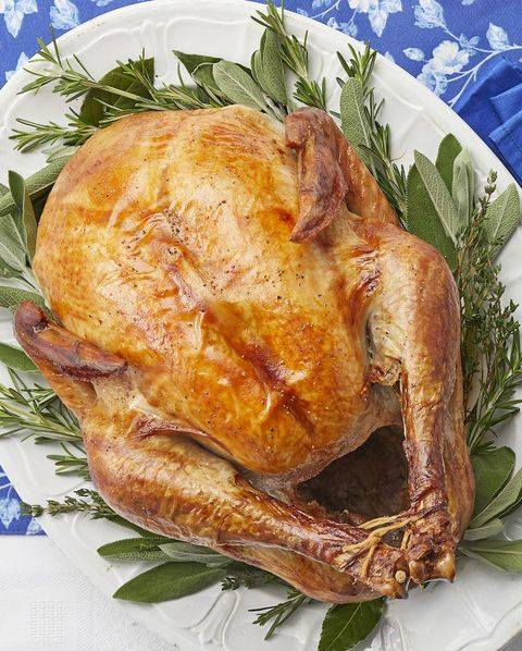 roasted thanksgiving turkey on white platter with blue linens