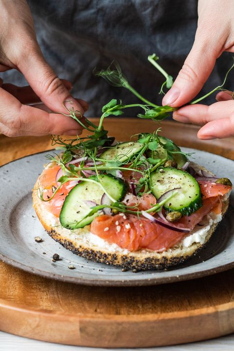 healthy toast with cream cheese, salmon, fresh cucumber, capers, red onion, black pepper and and an uncertain woman lays on sandwich pea sprouts