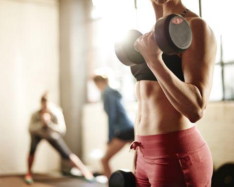 Mujer cogiendo peso en el gimnasio