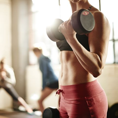healthy young female weight training in gym