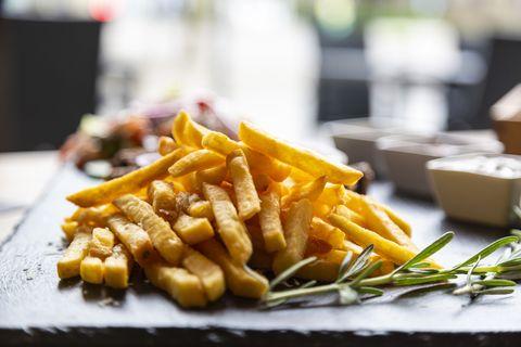 heap of crispy fried potato chips with rosemary
