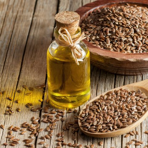 Heap of Flax seeds or linseeds in spoon and bowl with glass of linseed oil on wooden backdrop. Flaxseed or linseed concept. Flax seed dietary fiber