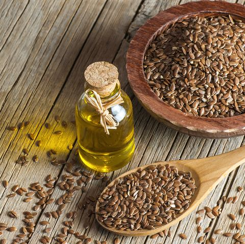heap of flax seeds or linseeds in spoon and bowl with glass of linseed oil on wooden backdrop flaxseed or linseed concept flax seed dietary fiber