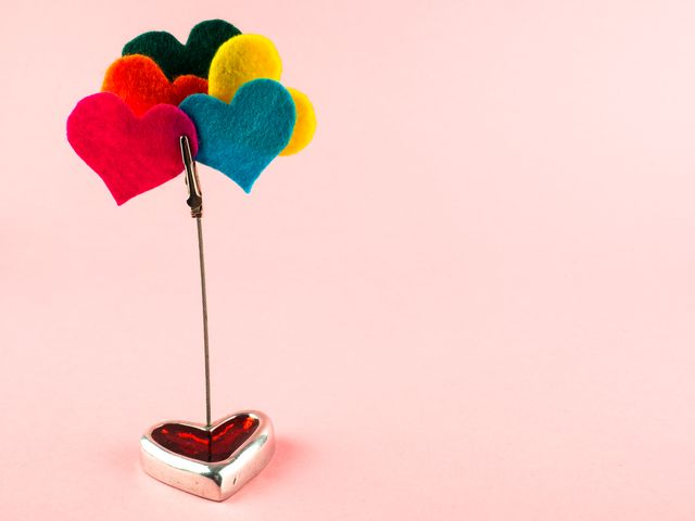 a heart shaped ornament and a clip with several felt colored hearts polyamory concept
