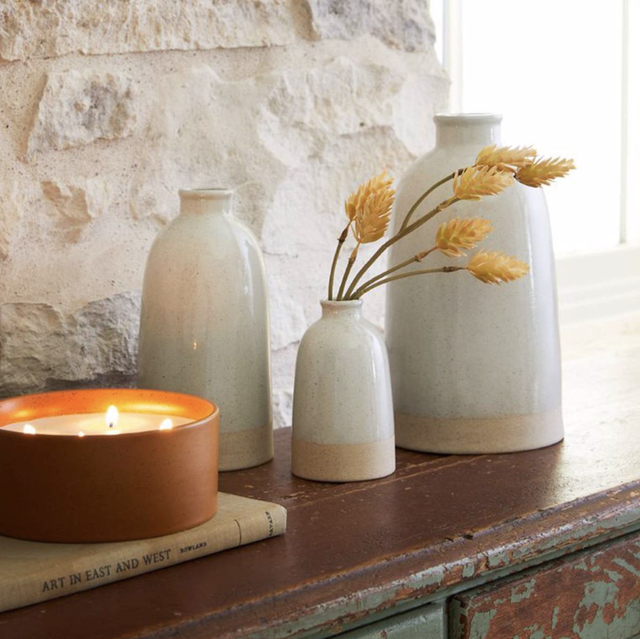 neutral stoneware vases next to lit candle