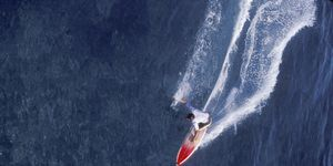 helicopter based overview of man surfing at Teahupoo in Tahiti