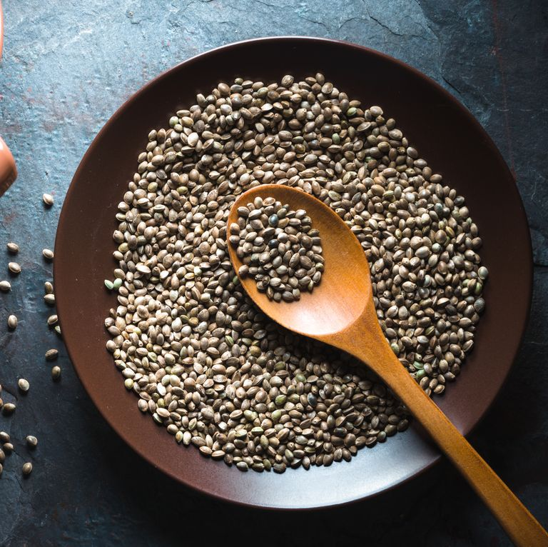 Hemp seeds on a plate and in a sieve on a gray blue stone